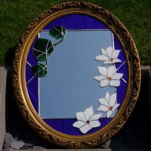 Gilt framed wooden mirror, blue border, large white flowers and green leaves