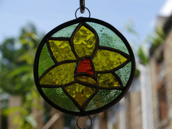 stained glass daffodil ornamentgreen background, yellow flower orange centre