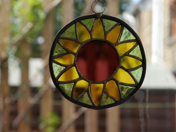 stained glass sunflower ornament round, green background, yellow petals purply centre