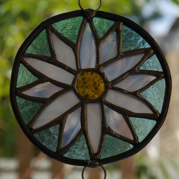 stained glass daisy ornament pale blue background, white streaky petal and yellow centre