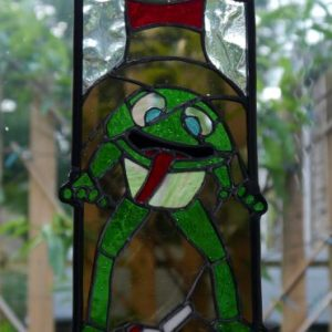Stained glass rally emblem Toads in a budweiser bottle with a discarded dogend, read budweiser lid hanging off th etop