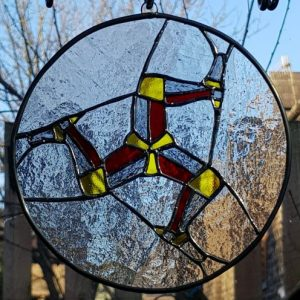 Bespoke stained glass Triskelion Three Legs of Mann clear background, grey yellow and red legs