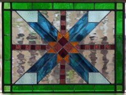 Quilt design, geometric blues, greens, clear, violet, purple and orange